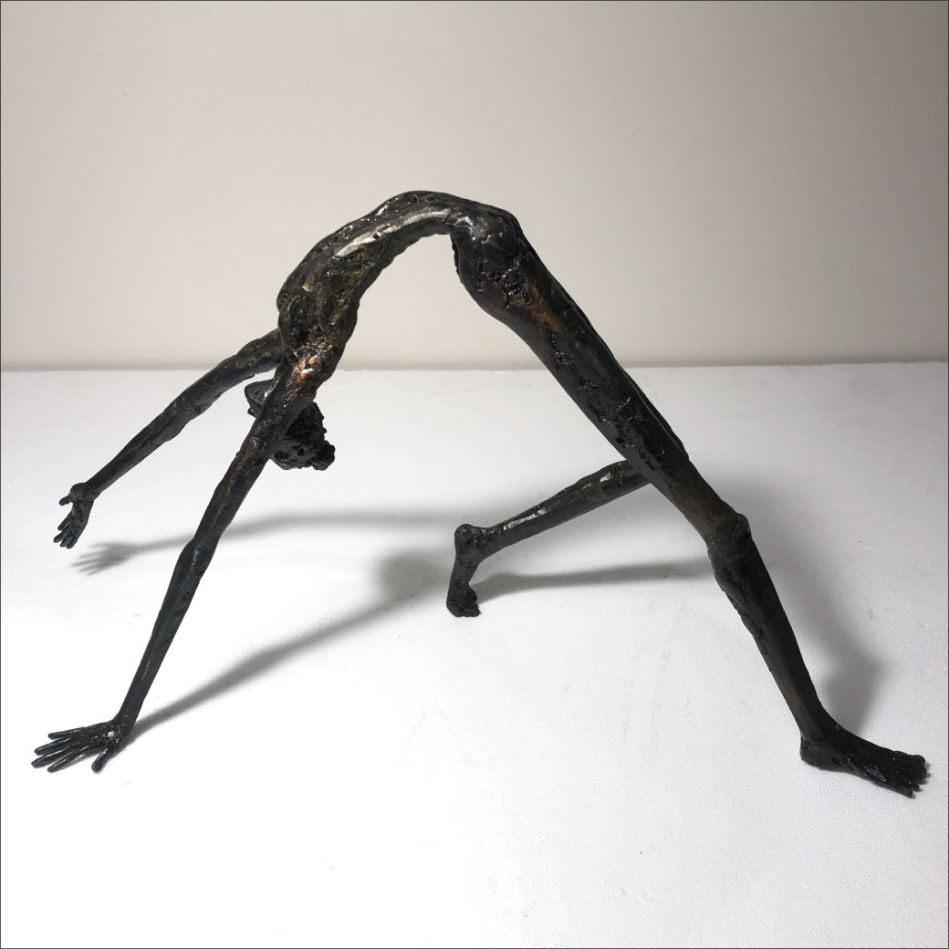 Steel sculpture by Tony O'Keefe. New Zealand artist. Figure doing yoga pose or backbend. Made of recycled steel.