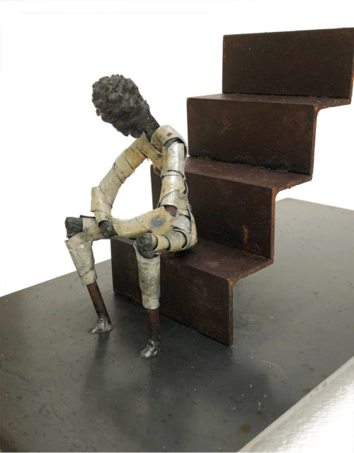 "Steel sculpture of a figure seated at the base of a flight of stairs. Titled ""Stoop"". By Tony O'Keefe. Artist from Queenstown, New Zealand."
